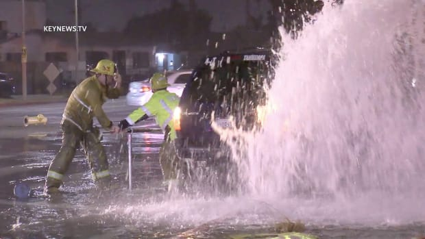 Firefighters Work to Turn Off Water After Vehicle Collision with Hydrant