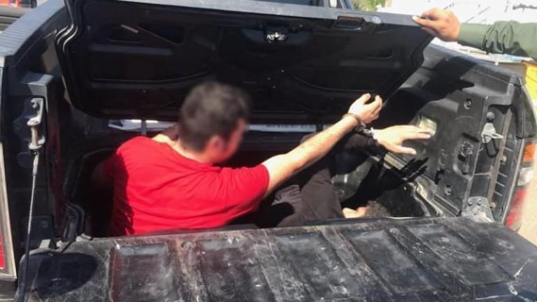 HUMAN SMUGGLERS HIDE ILLEGAL IMMIGRANTS IN BED OF TRUCK