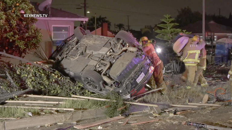 Two Persons Trapped After Vehicle Rollover into Backyard